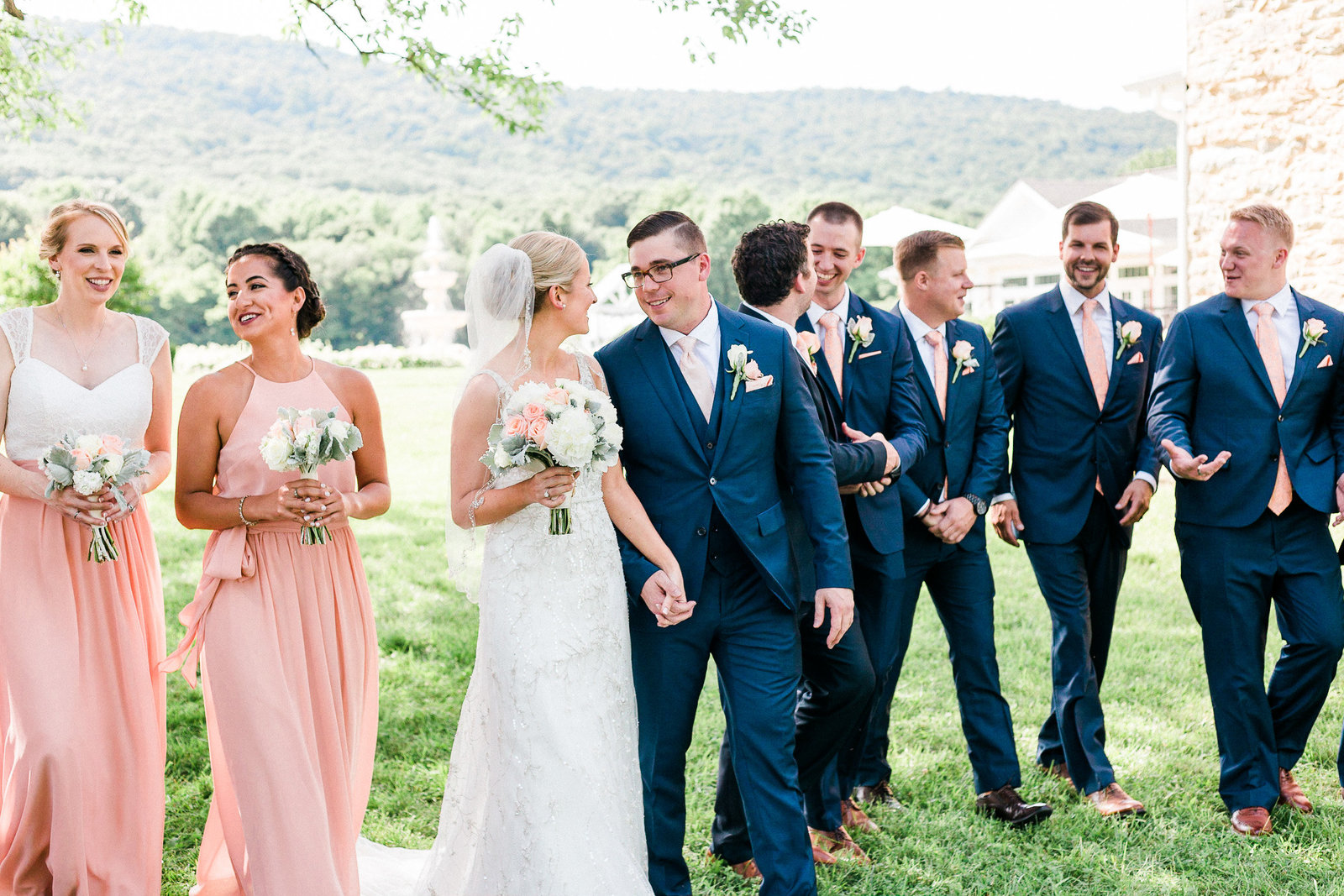 Bridal party in pink dresses and navy suits  walk with the bride and groom at Springfield Manor Maryland