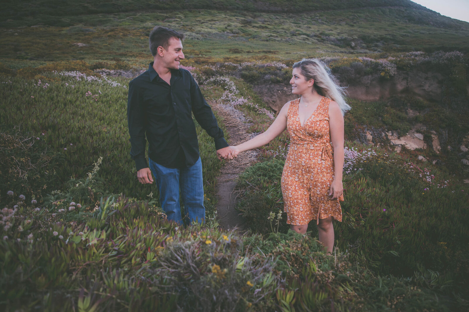 Couple hold hands and look at each other during sunset in Big Sur.