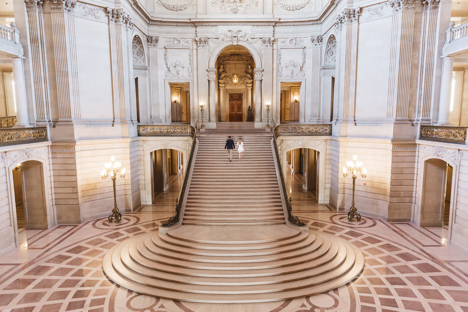 wide shot of couple on stairs at san francisco city hall