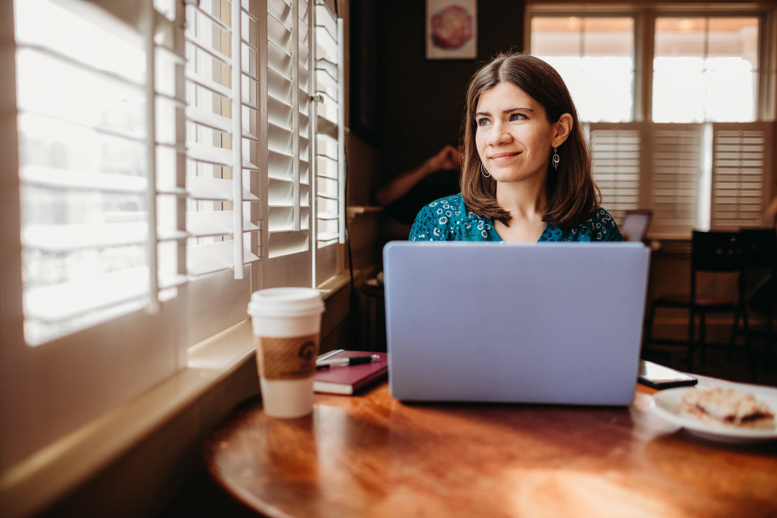 woman works at coffee shop during marketing photo session