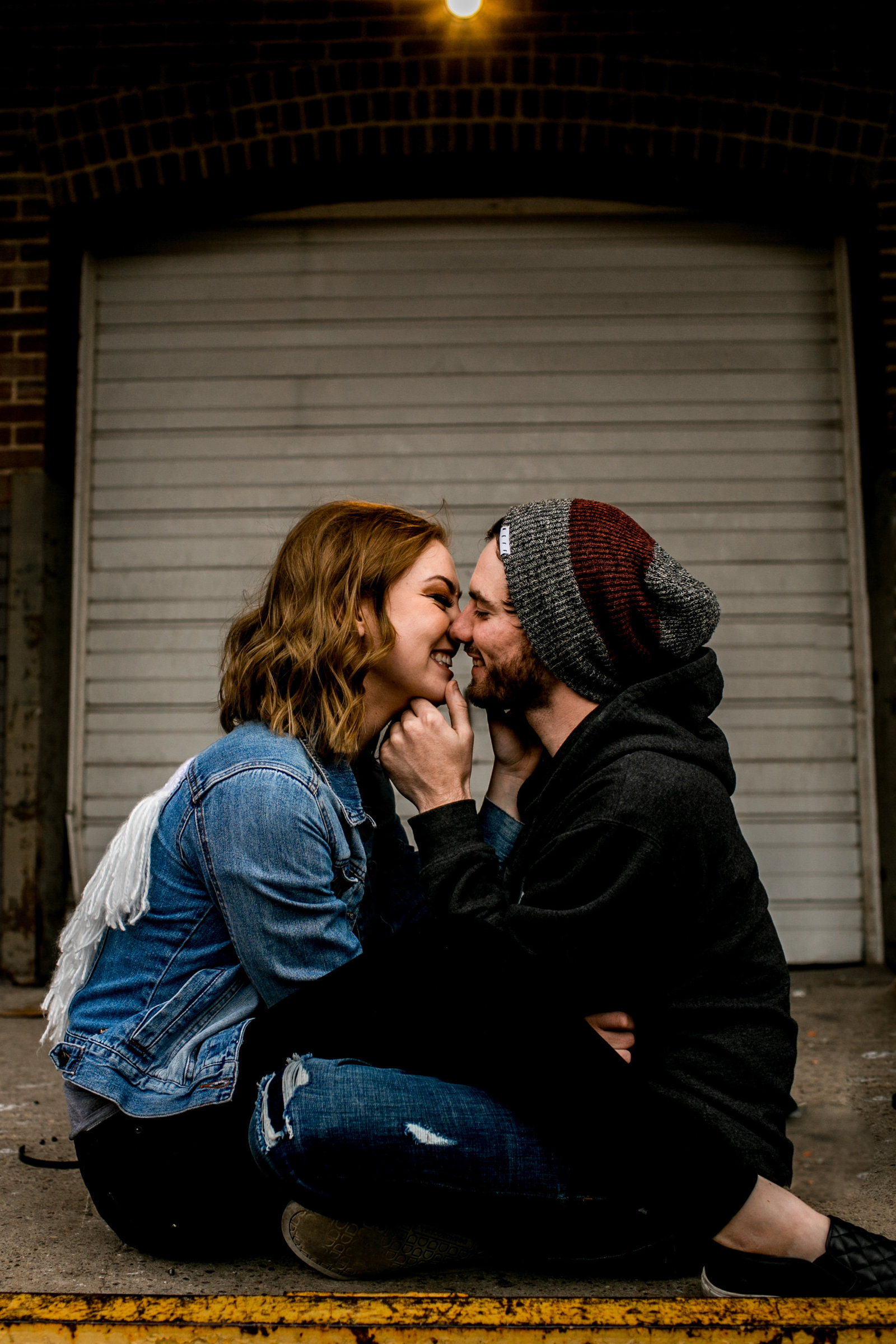 Engaged couple cuddling together in an industrial place in Minneapolis Minnesota.