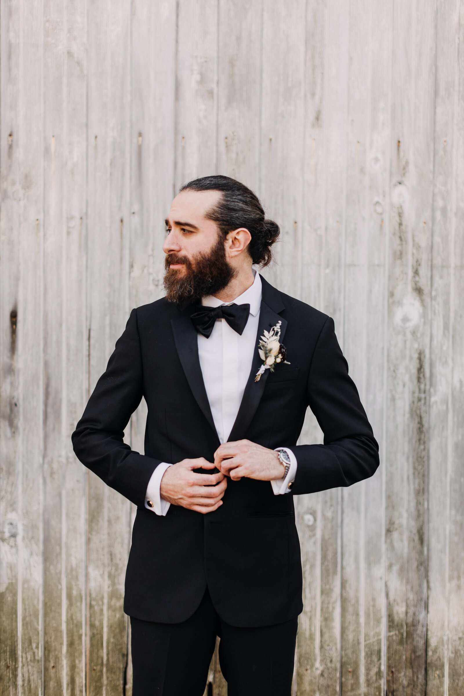 groom in tux at old barn
