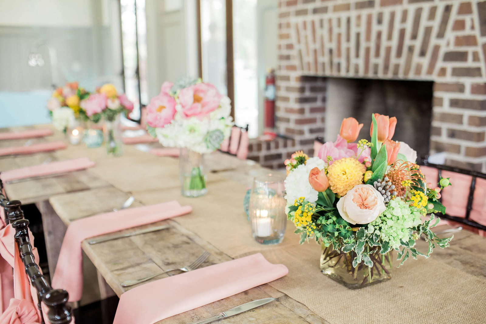Orange, yellow, and pink floral arrangement is placed on each table, I'on Creek Club, Charleston Wedding Photographer.