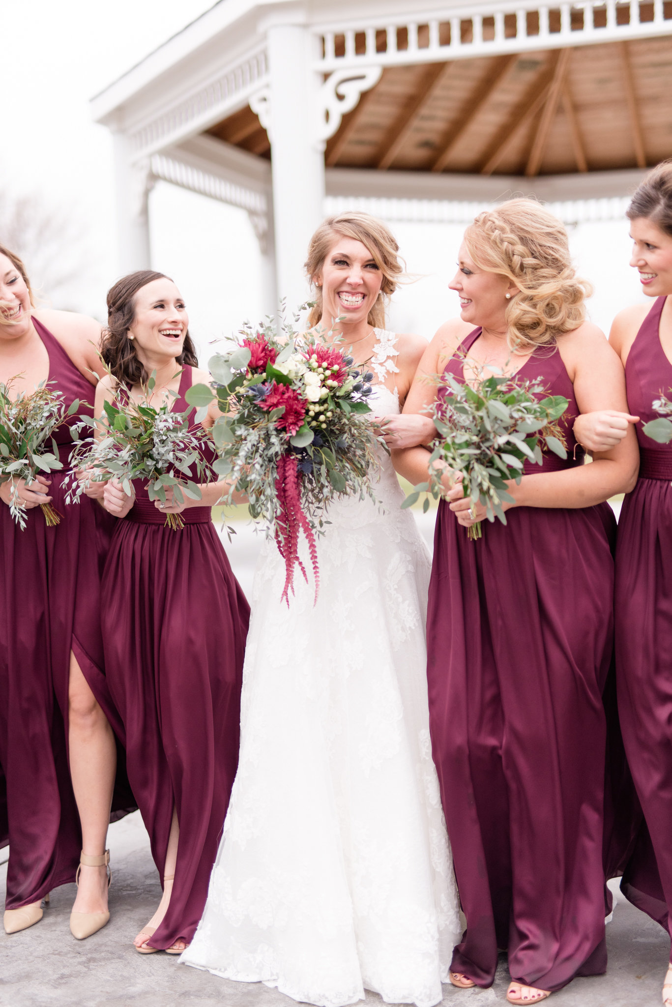 Bride and bridesmaids laugh while walking.