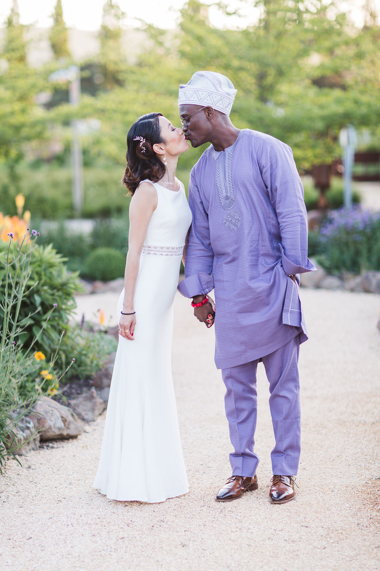 japanese bride and nigerian groom kissing in the formal grounds of cornerstone sonoma
