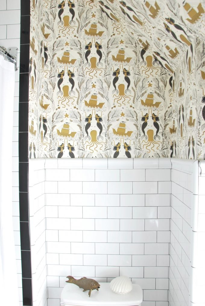 A wallpapered bathroom with subway tile.