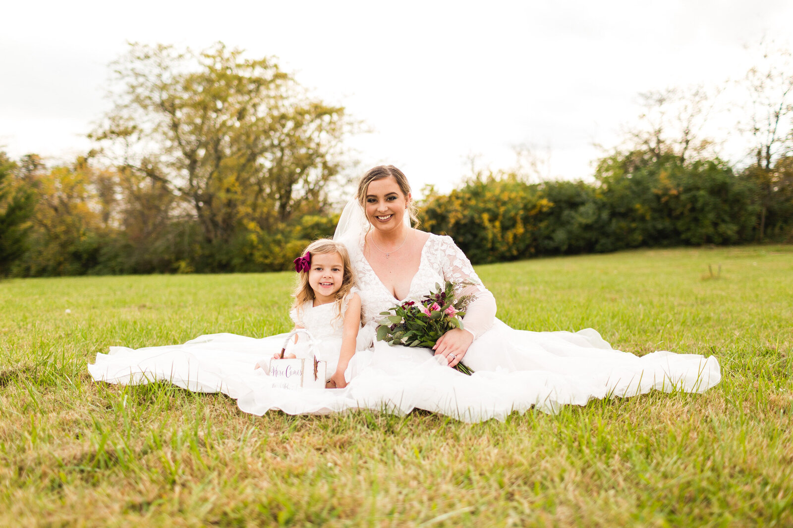 bride and flower girl sitting for portrait together ohio