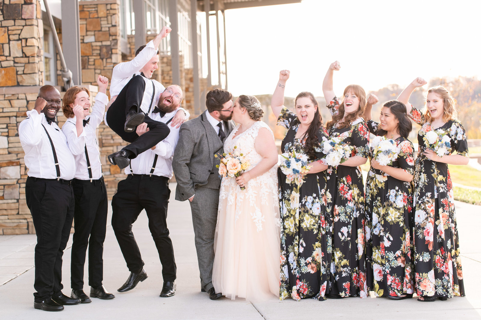 couple kissing while bridal party celebrates and cheers