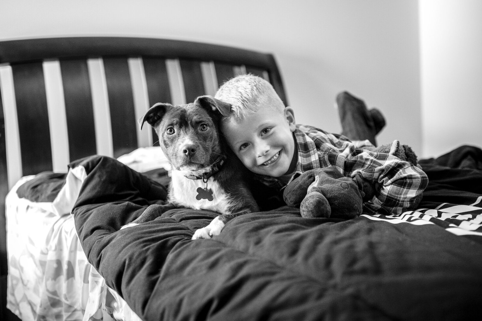 a boy poses with his dog in his bedroom