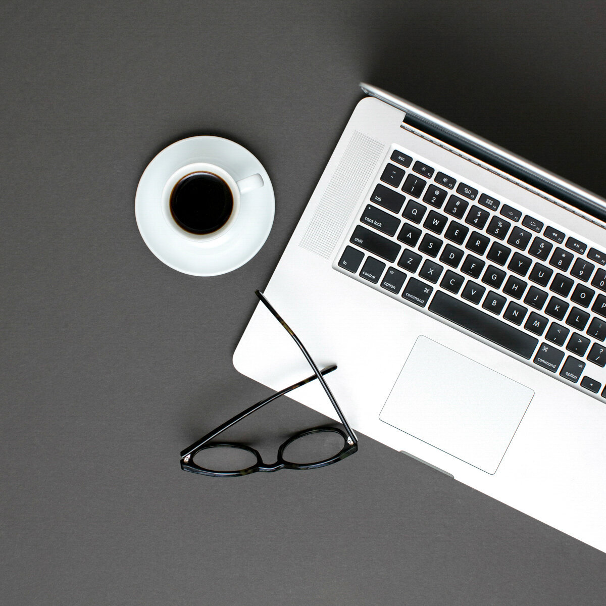 mac book next to a black cup of coffee on a grey background