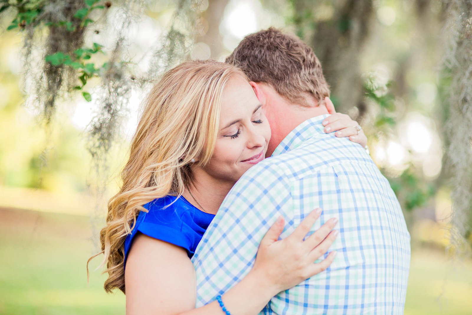 Engaged couple cuddle under a tree with spanish moss, Hampton Park, Charleston, South Carolina