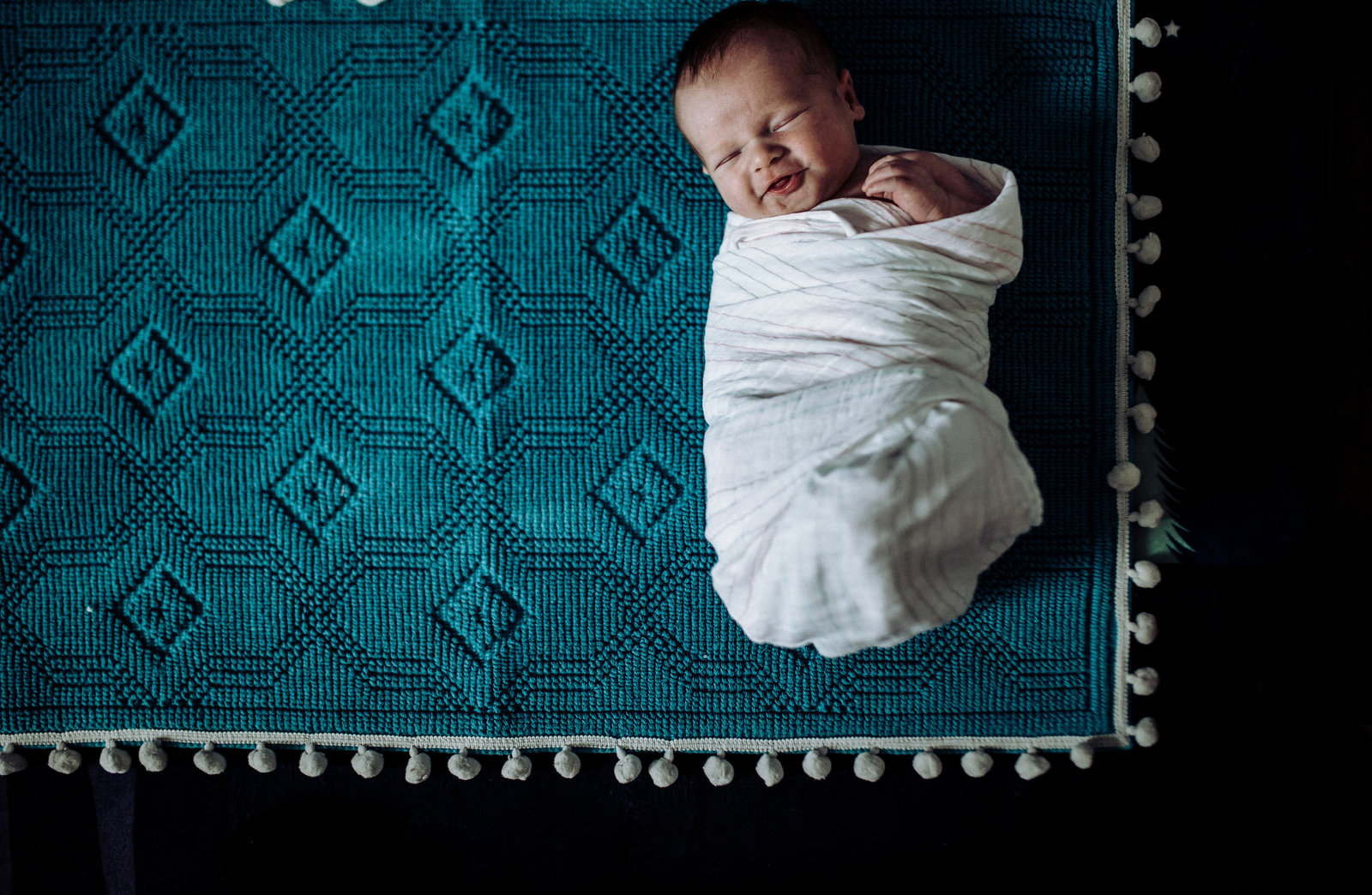 newborn baby session baby smiling laying on Target ornate rug