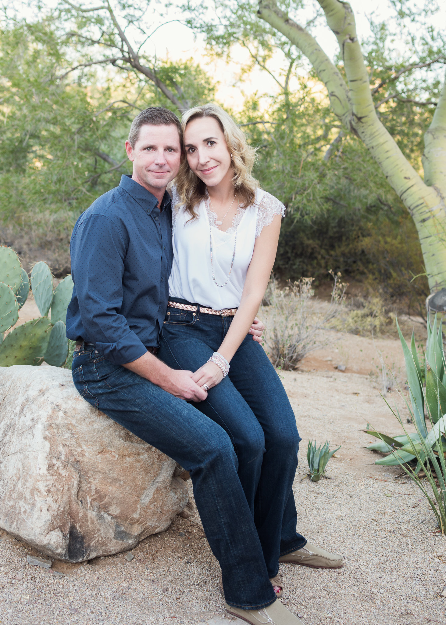 husband and wife sitting on a boulder in the desert
