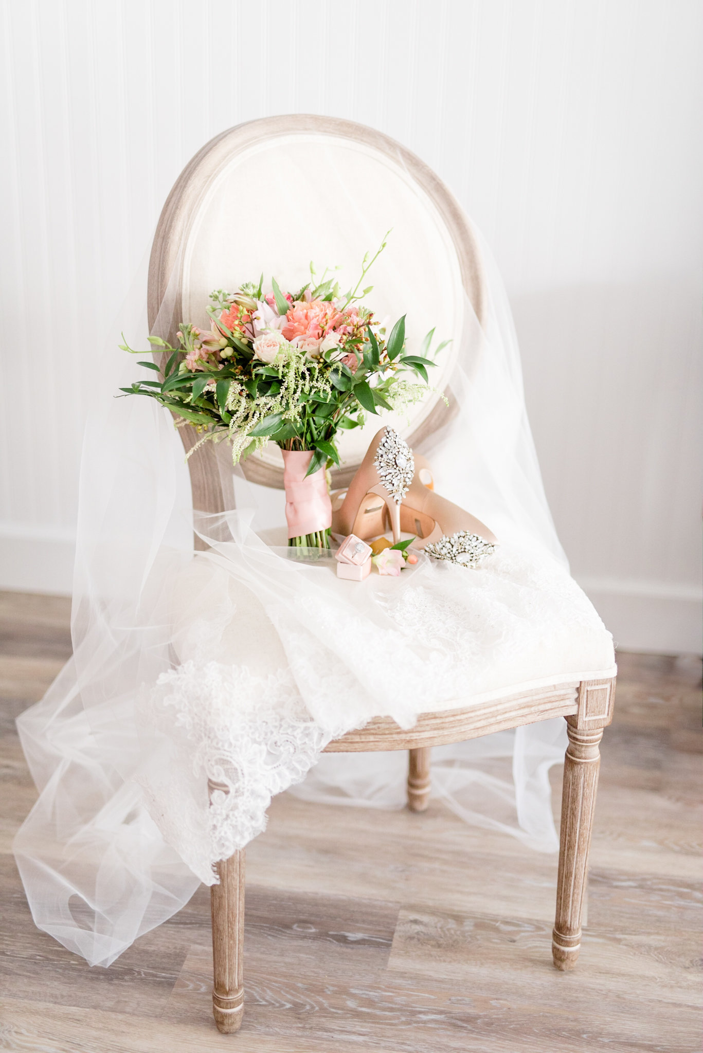 Bouquet and wedding heels sit on chair.