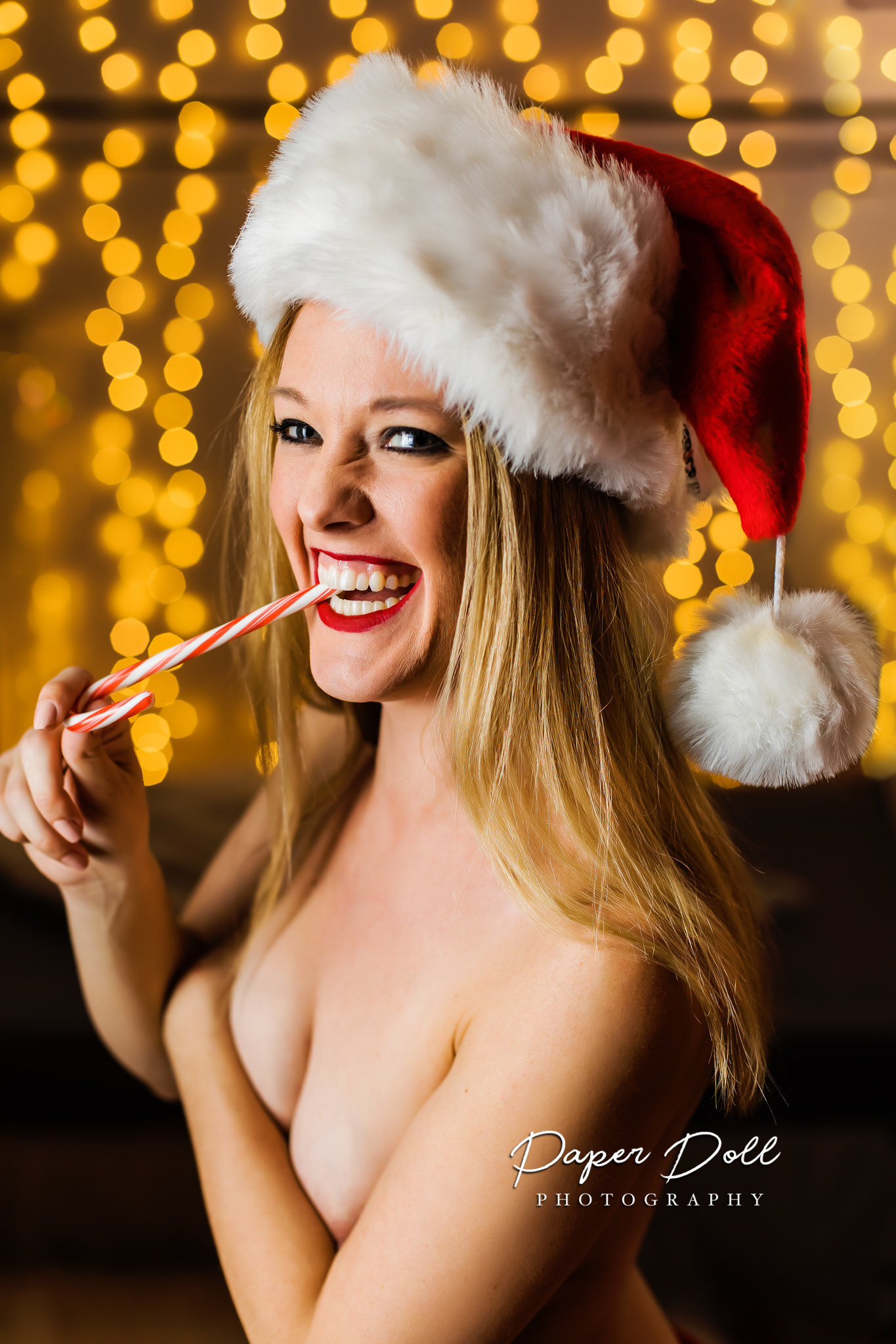 Happy topless woman wearing a Santa hat and eating a candy cane