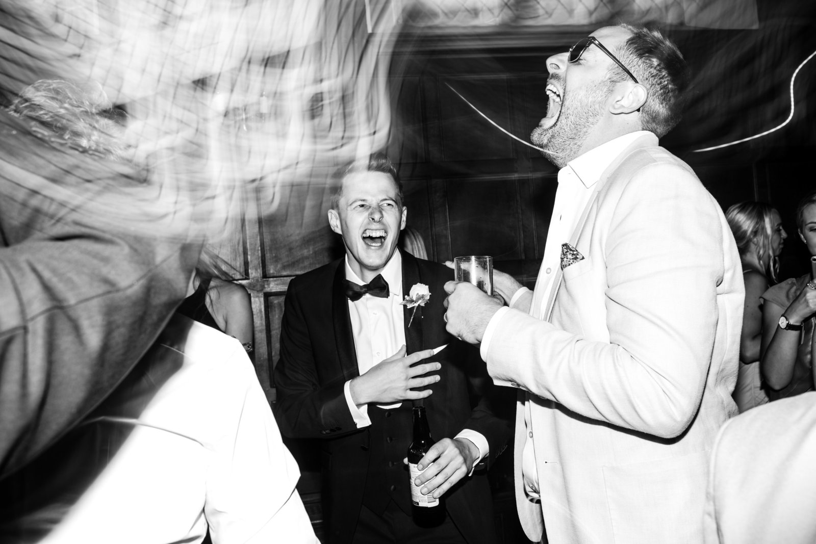 Evening suited wedding guests laugh on the dance floor at Hengrave Hall, Suffolk.