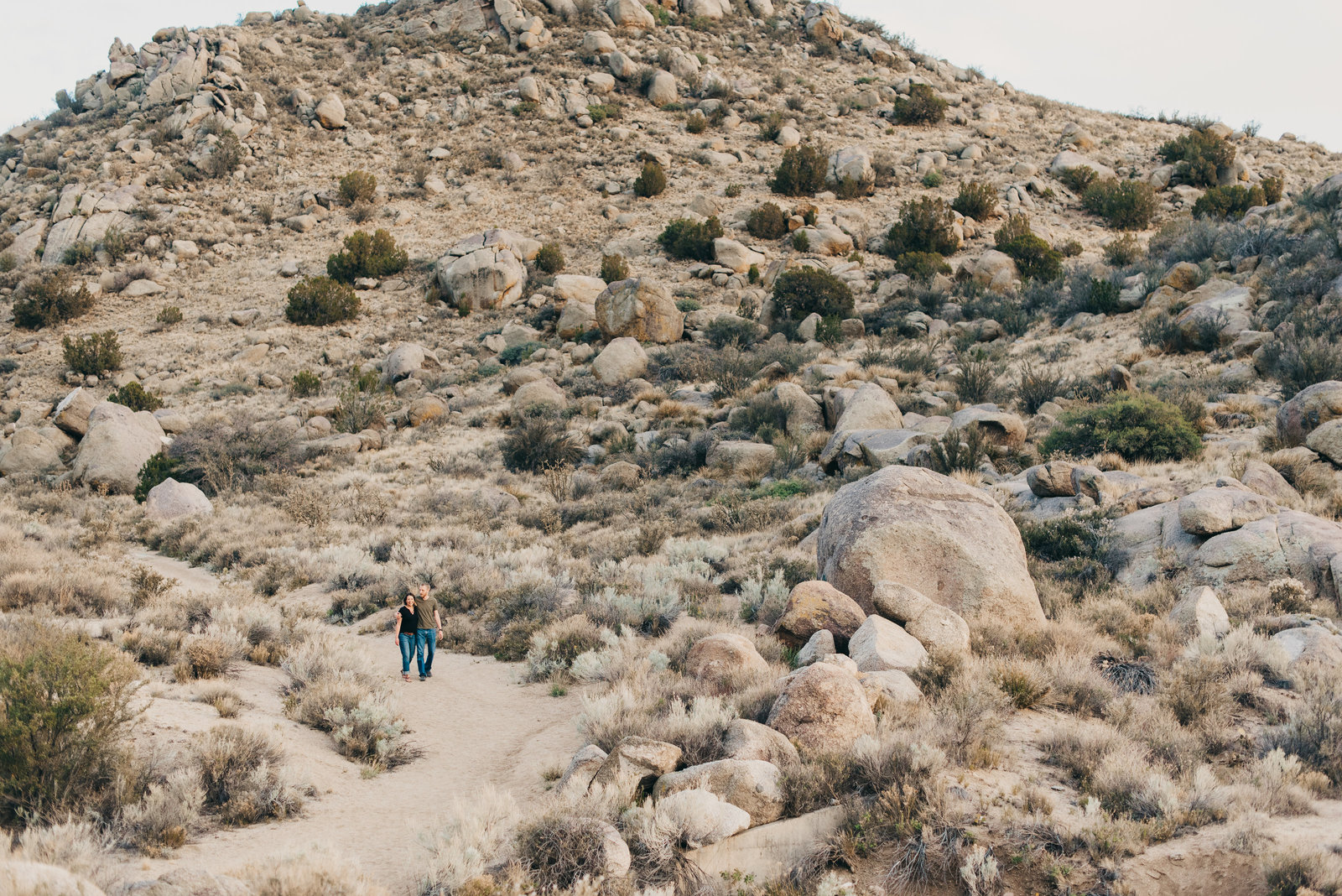 Couple walking through the  Sandia Mountain Foothills desert