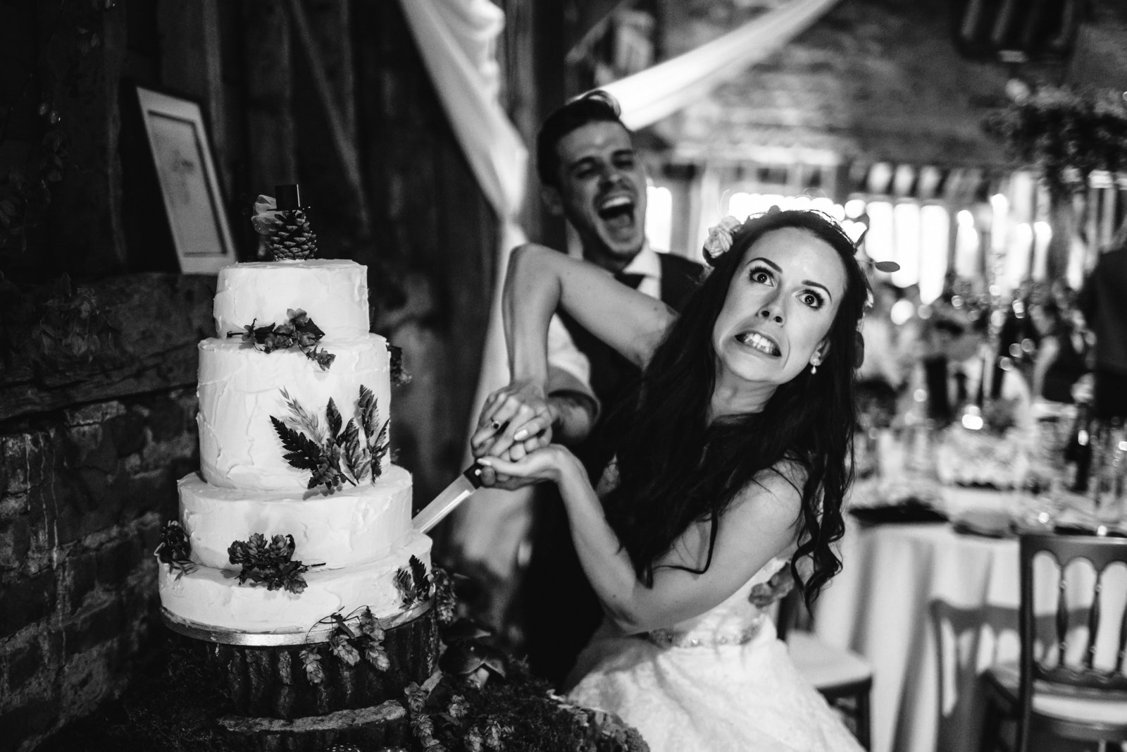 A Bride pulls a funny face while cutting her wedding cake at Suffolk Barn Hawstead