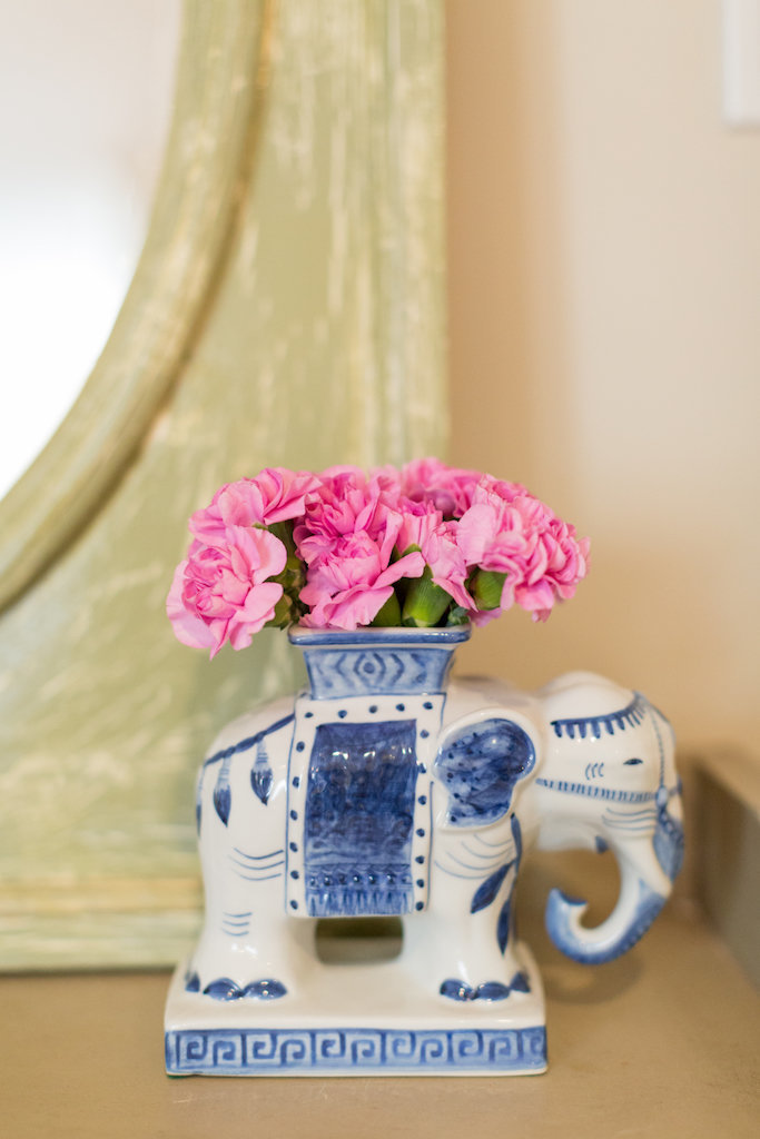 A white and blue ceramic elephant vase with pink flowers.