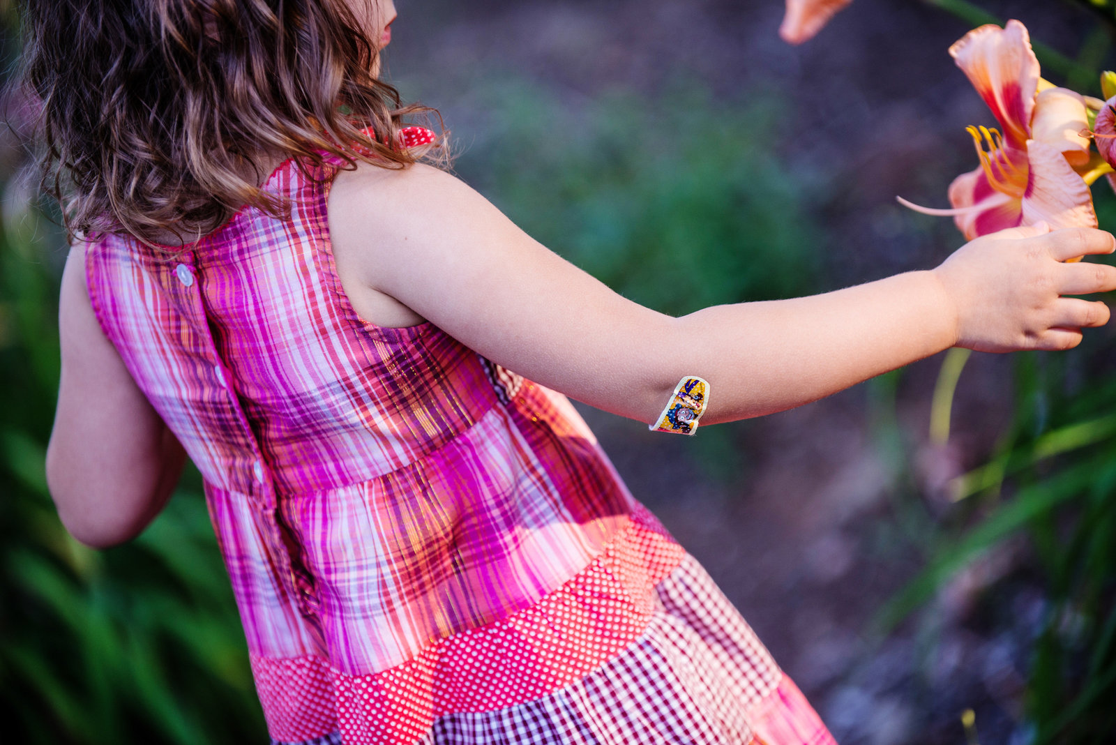 a little girl picks a flower with a band-aid on her elbow