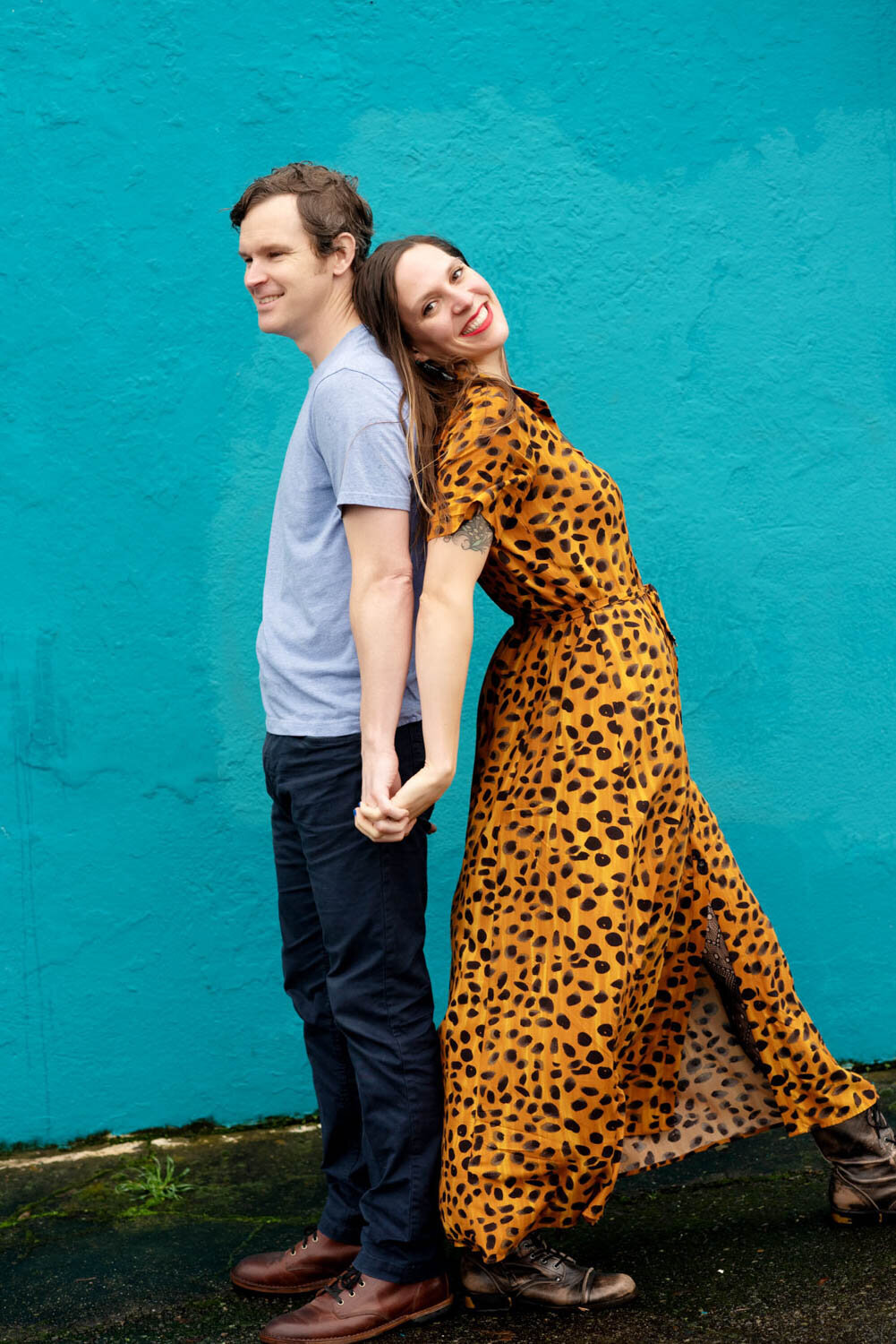 a woman in a leopard dress leans against a man in front of a bright blue wall
