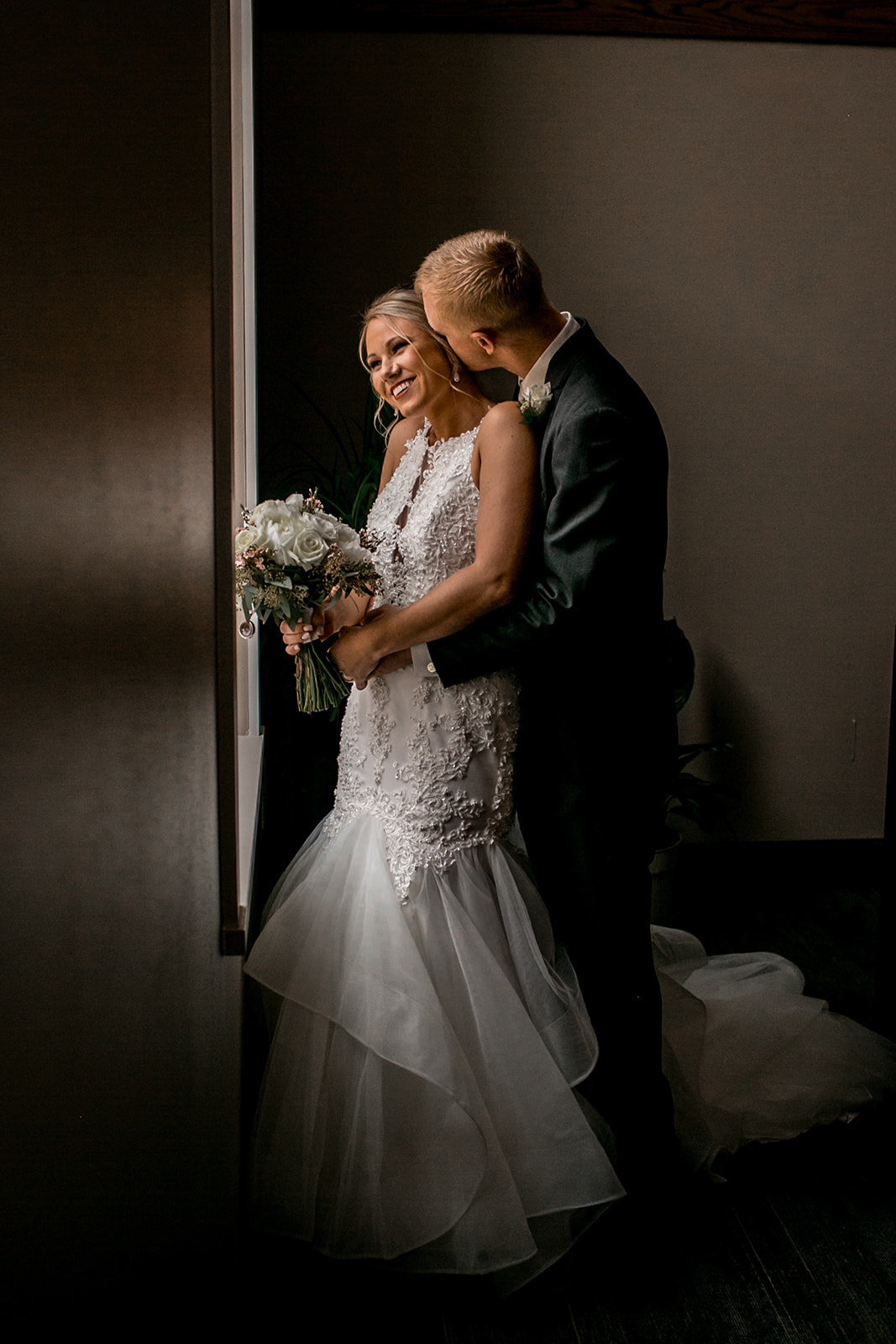 Des Moines Iowa wedding couple cuddling by the window.