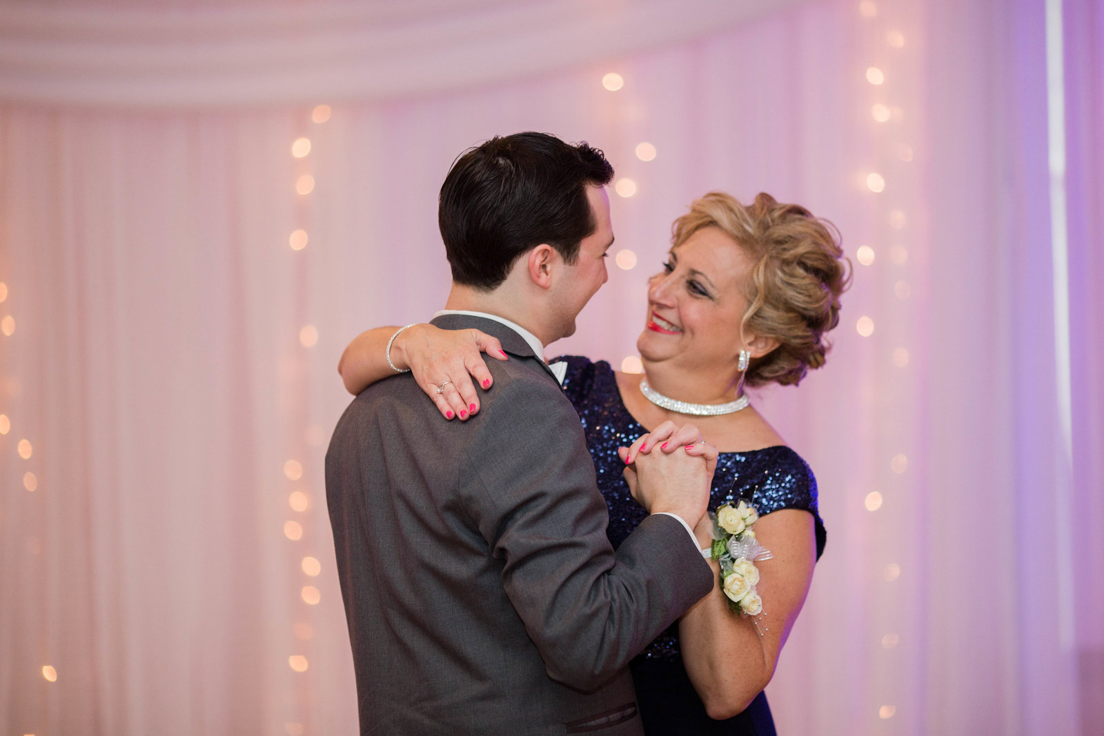 groom dances with his mom in front of a sheer purple backdrop with twinkle lights