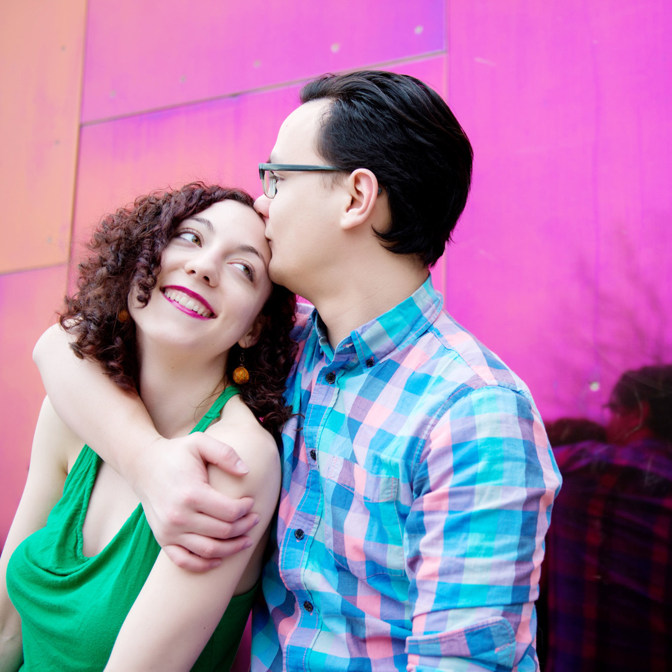 a man kisses a woman's forehead in front of a bright pink shiny wall