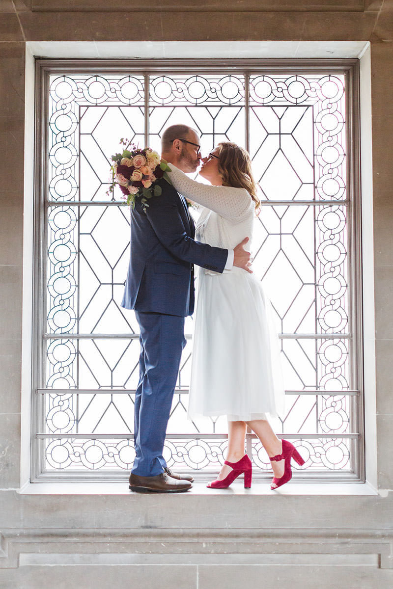 couple with bride in red shoes framed perfectly inside picture windows on 3rd floor of city hall