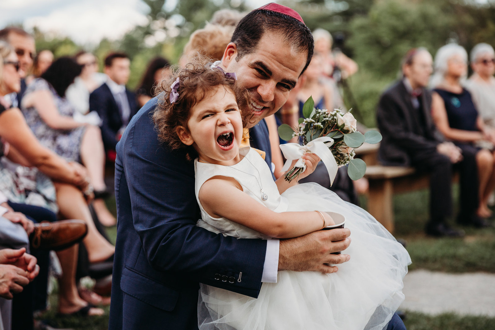 man holds laughing flower girl during wedding ceremony in boston ma