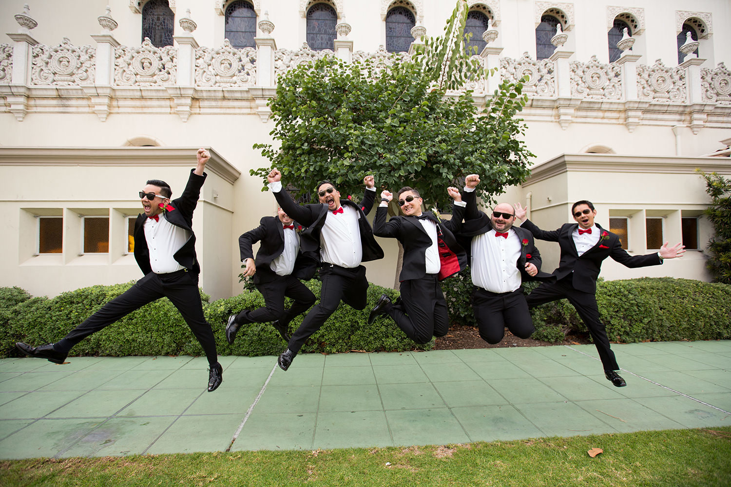 groomsmen jumping in front of the immaculata