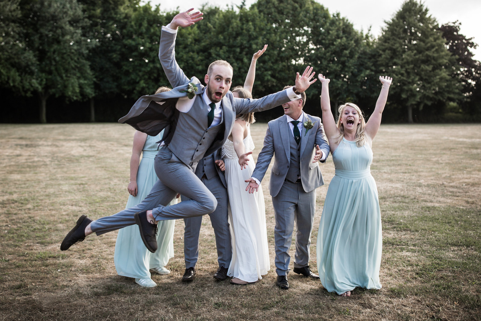The wedding party stand on a field in Norfolk and one of the Groomsman throws himself in front of the photo.