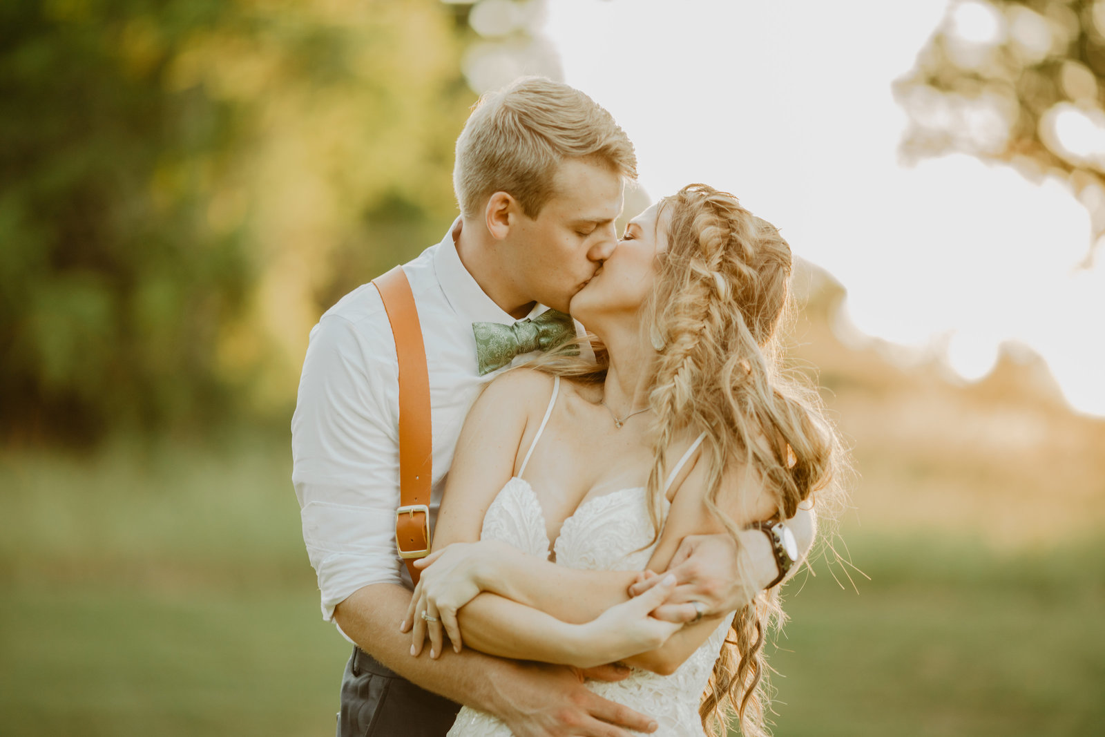 Groom wraps up and kisses Bride in field at Ravenswood Mansion