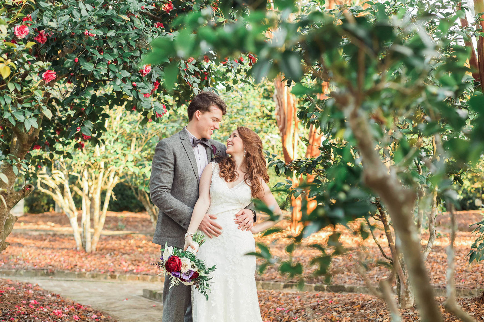 Bride and groom stand in garden at sunset, Boone Hall Plantation, Charleston, South Carolina