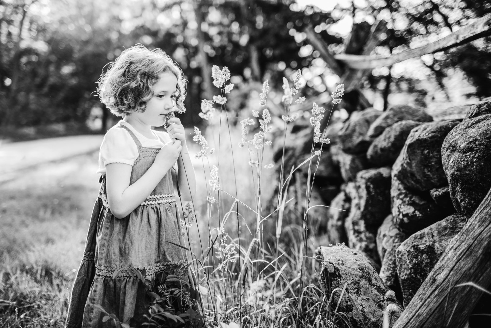 black and white portrait of girl smelling flowers at sunset