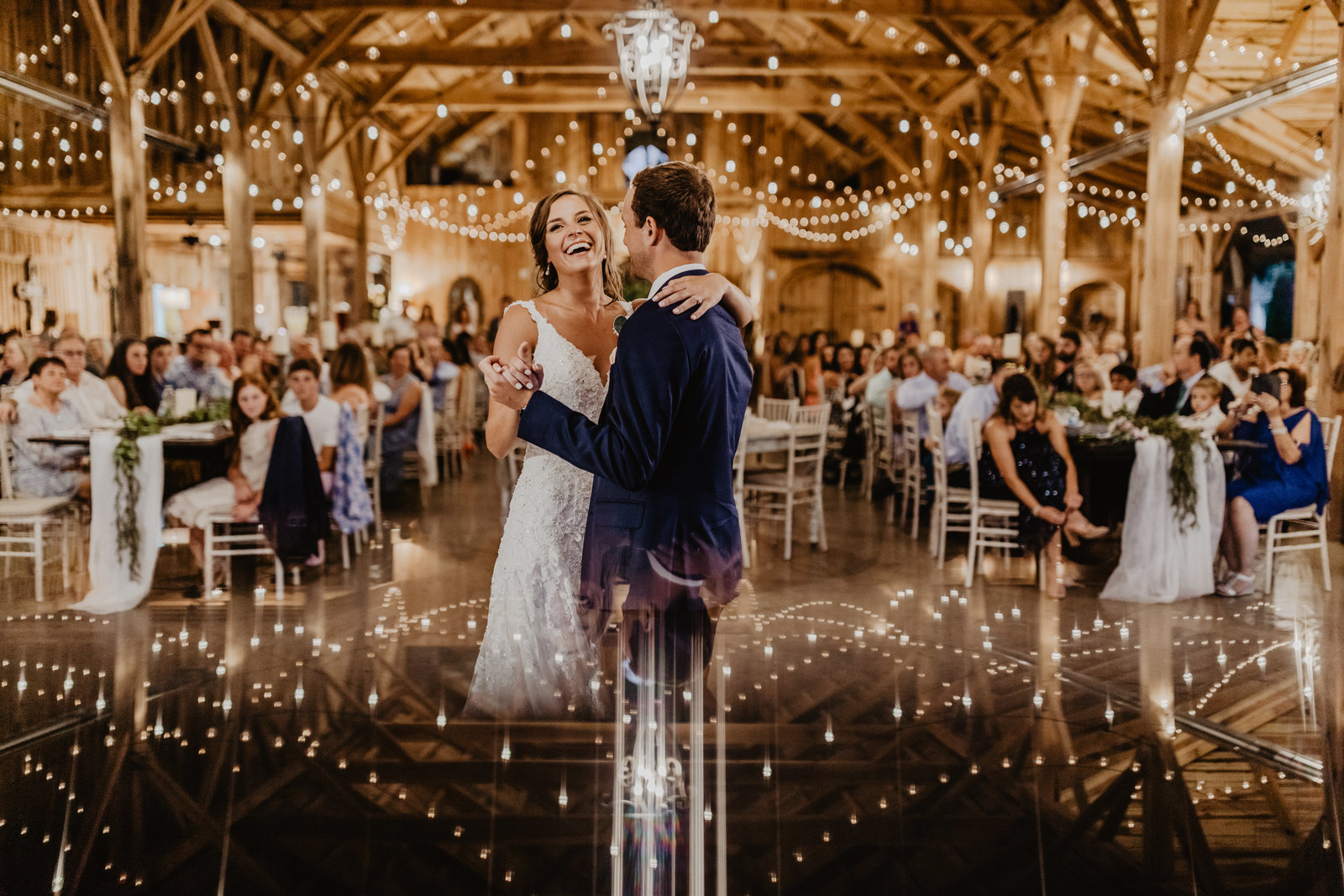 Bride and Groom enjoying their first dance with epic reflection of string lights at Cason's Cove