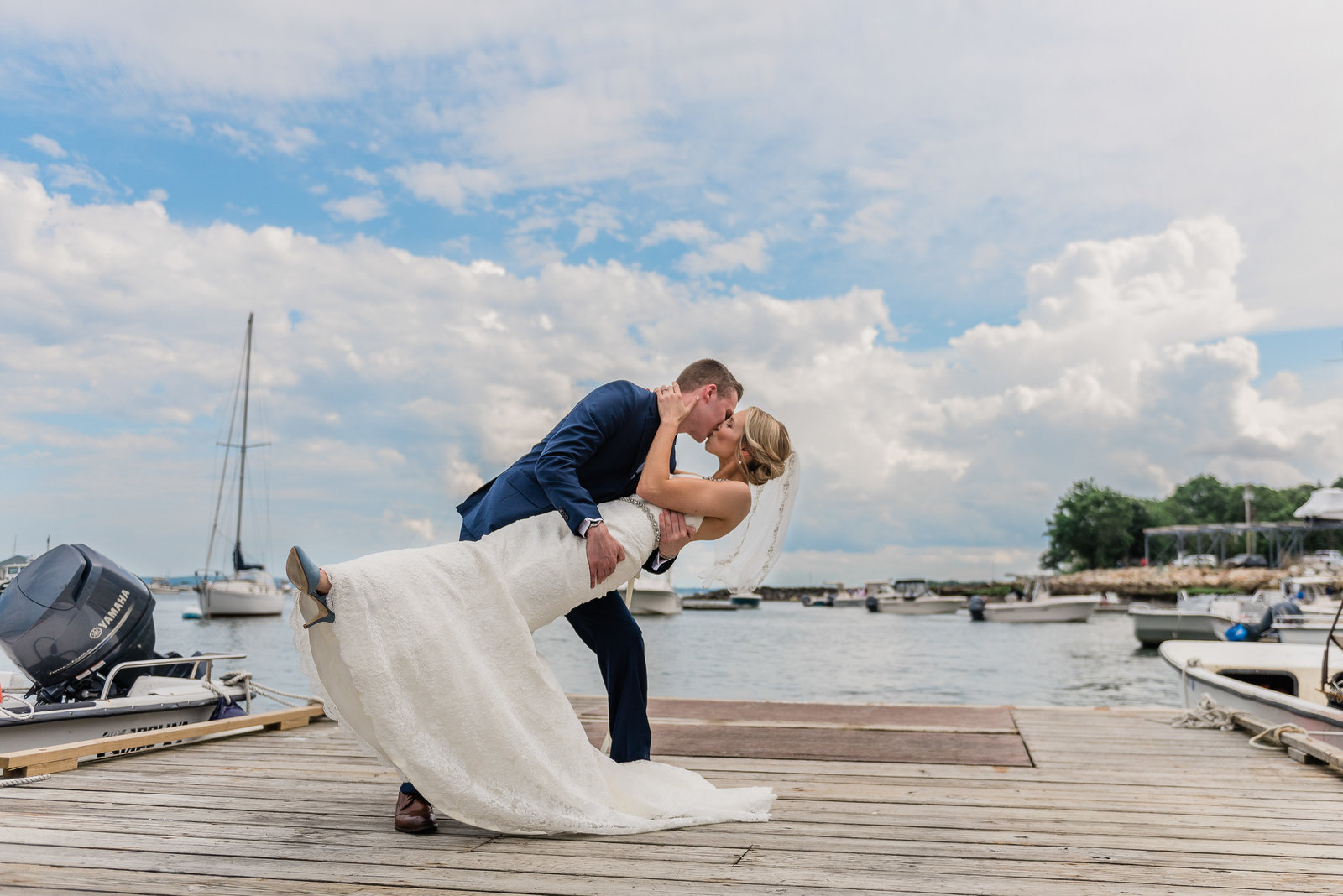 Wedding couple dip on the dock at a Duxbury Bay Maritime School wedding