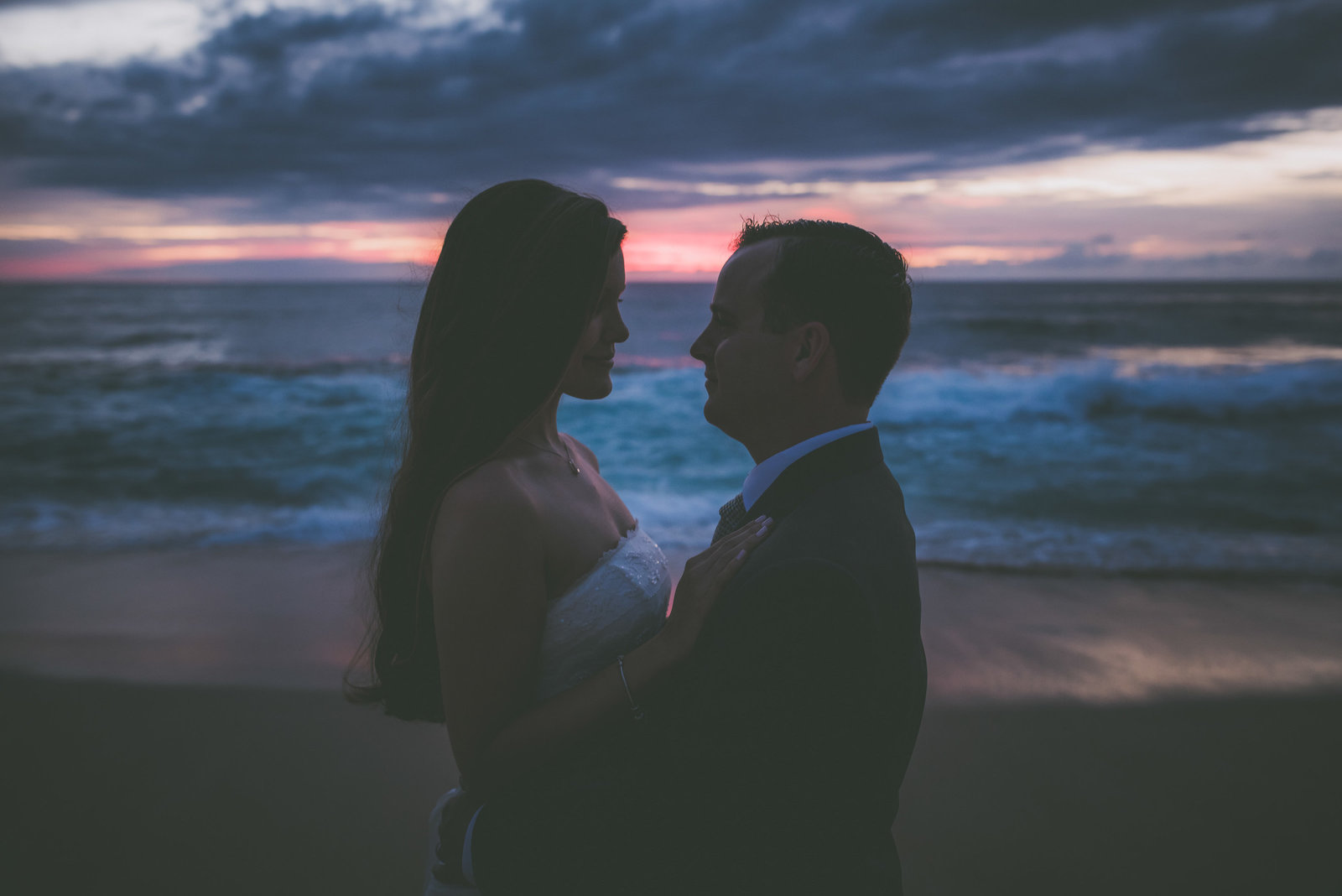 Newly weds gaze at each other during sunset on a beach.