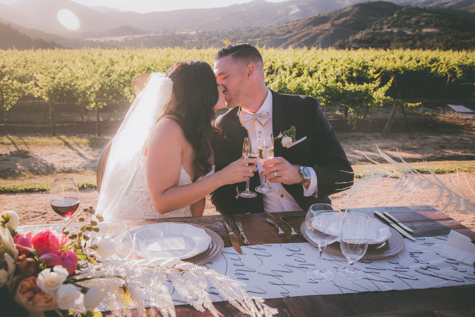 A kiss shared between bride and groom while cheering glasses at a Carmel vineyard.