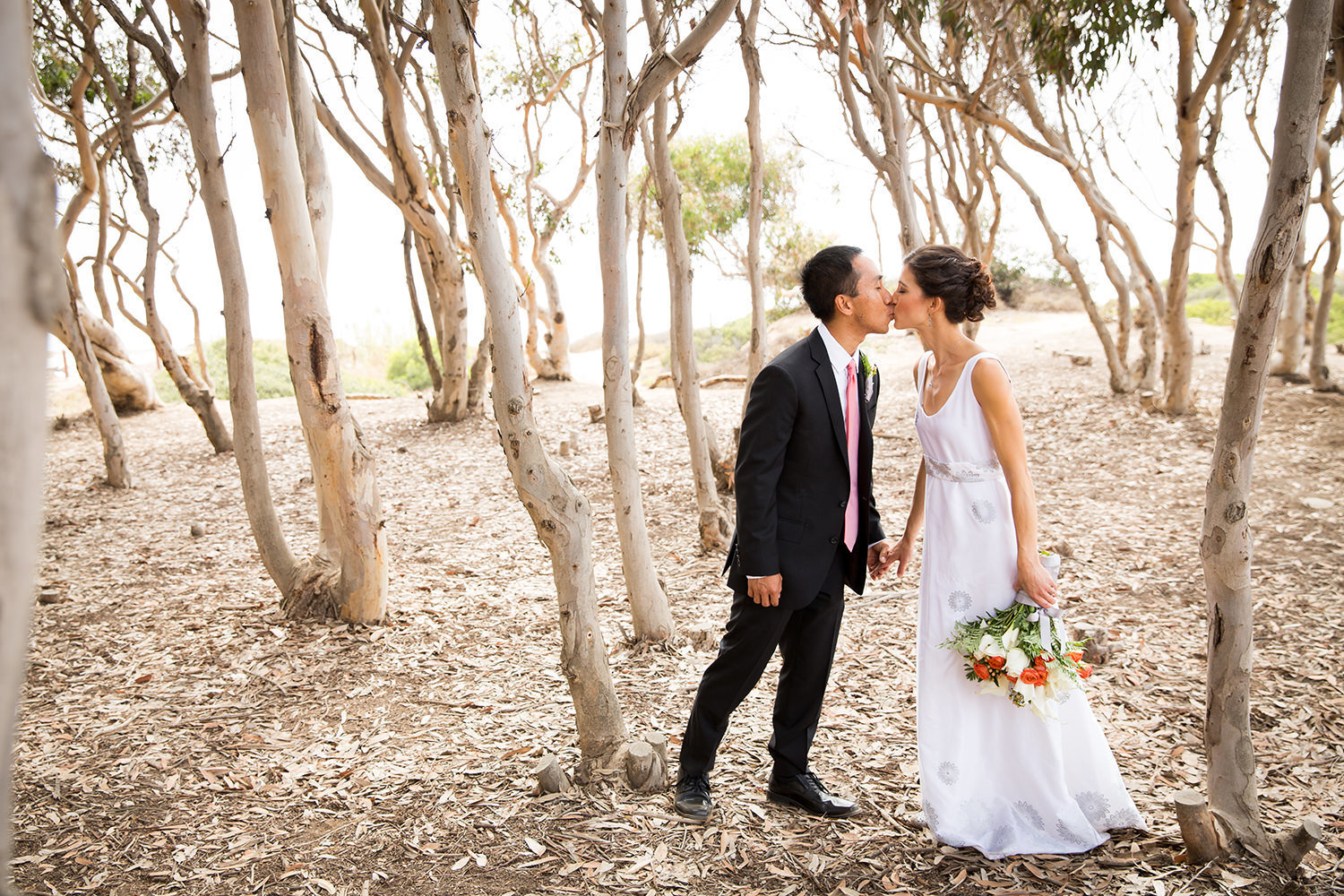 bride and groom kissing with trees at sunset cliffs