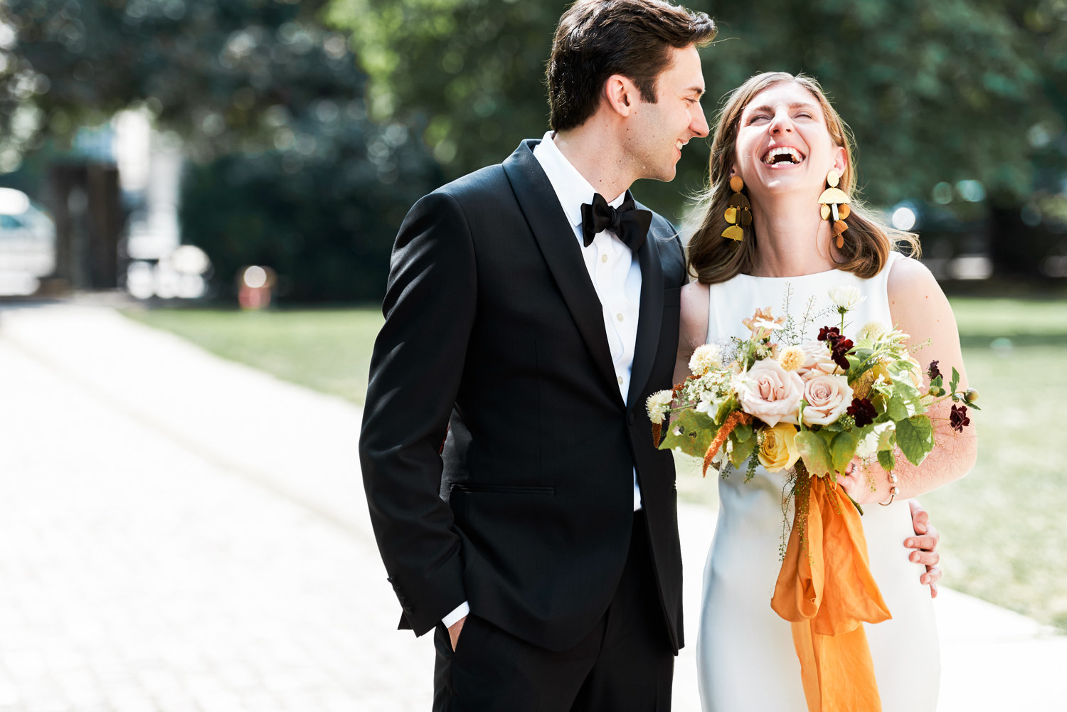Bride and groom laughing with orange flowers at osgoode hall