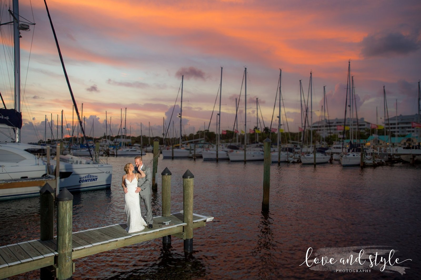 Riverhouse Reef and Grill Wedding Photography, bride and groom portrait on the dock with boats and sunset in the background