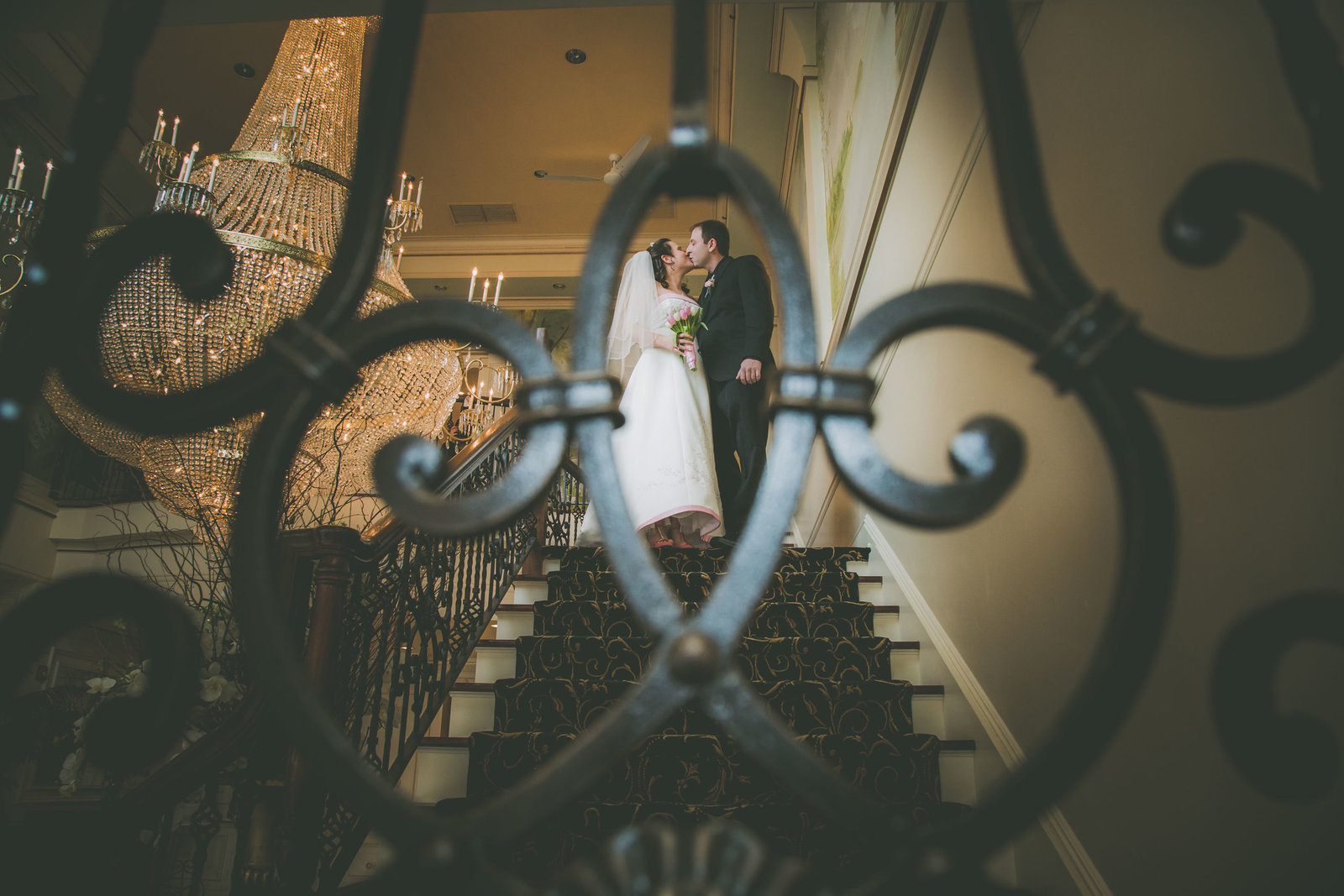 Bride and groom are framed within railing on stairway while they kiss.