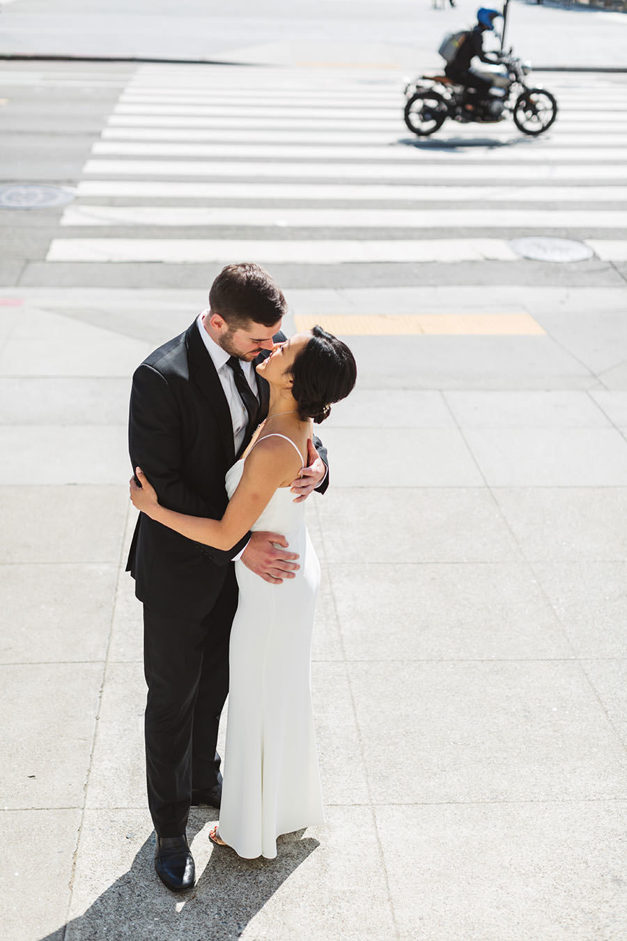 Couple kissing outside San Francisco City Hall before their wedding ceremony