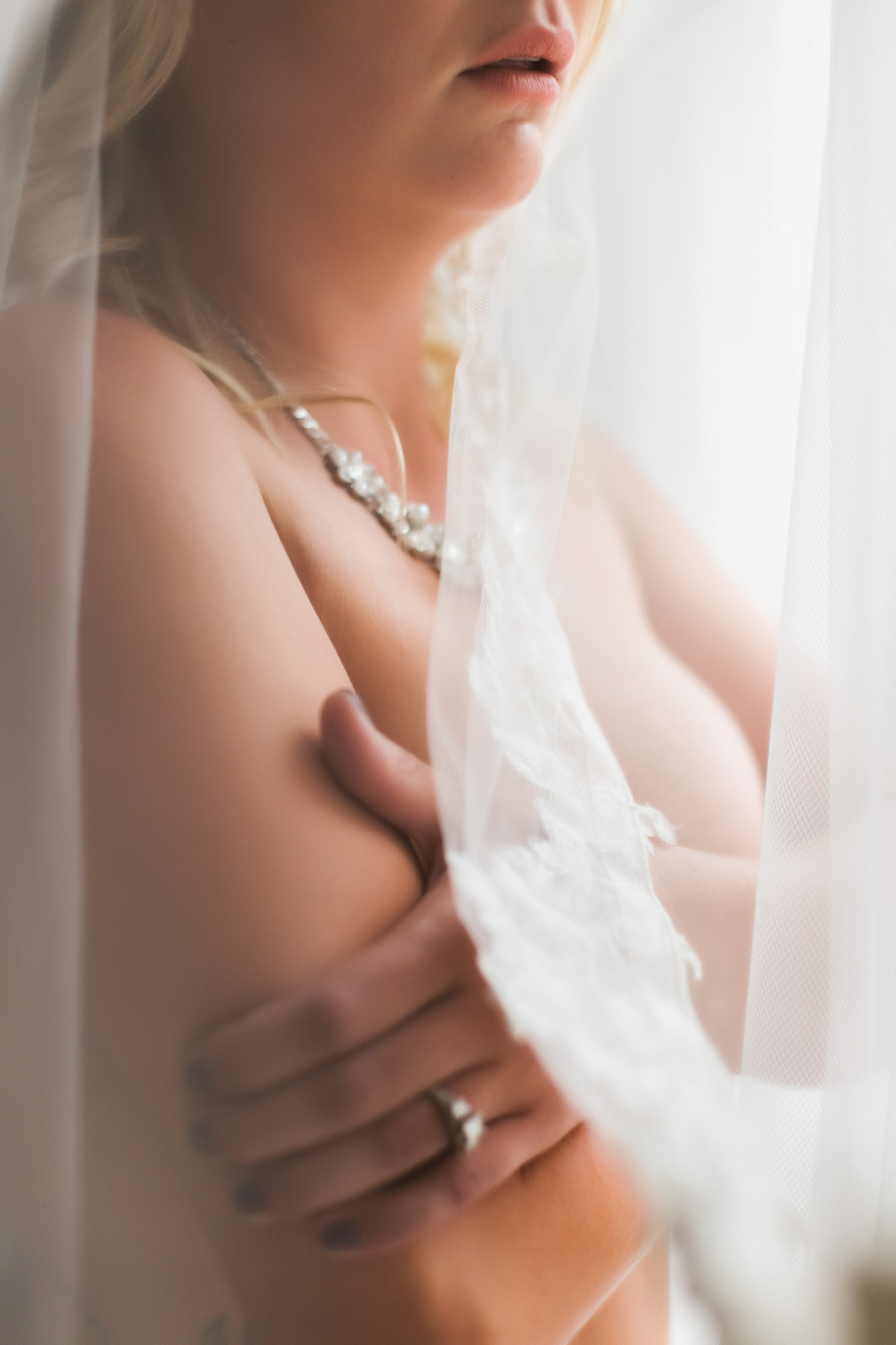 Romantic bridal boudoir photo of a bride wearing her veil