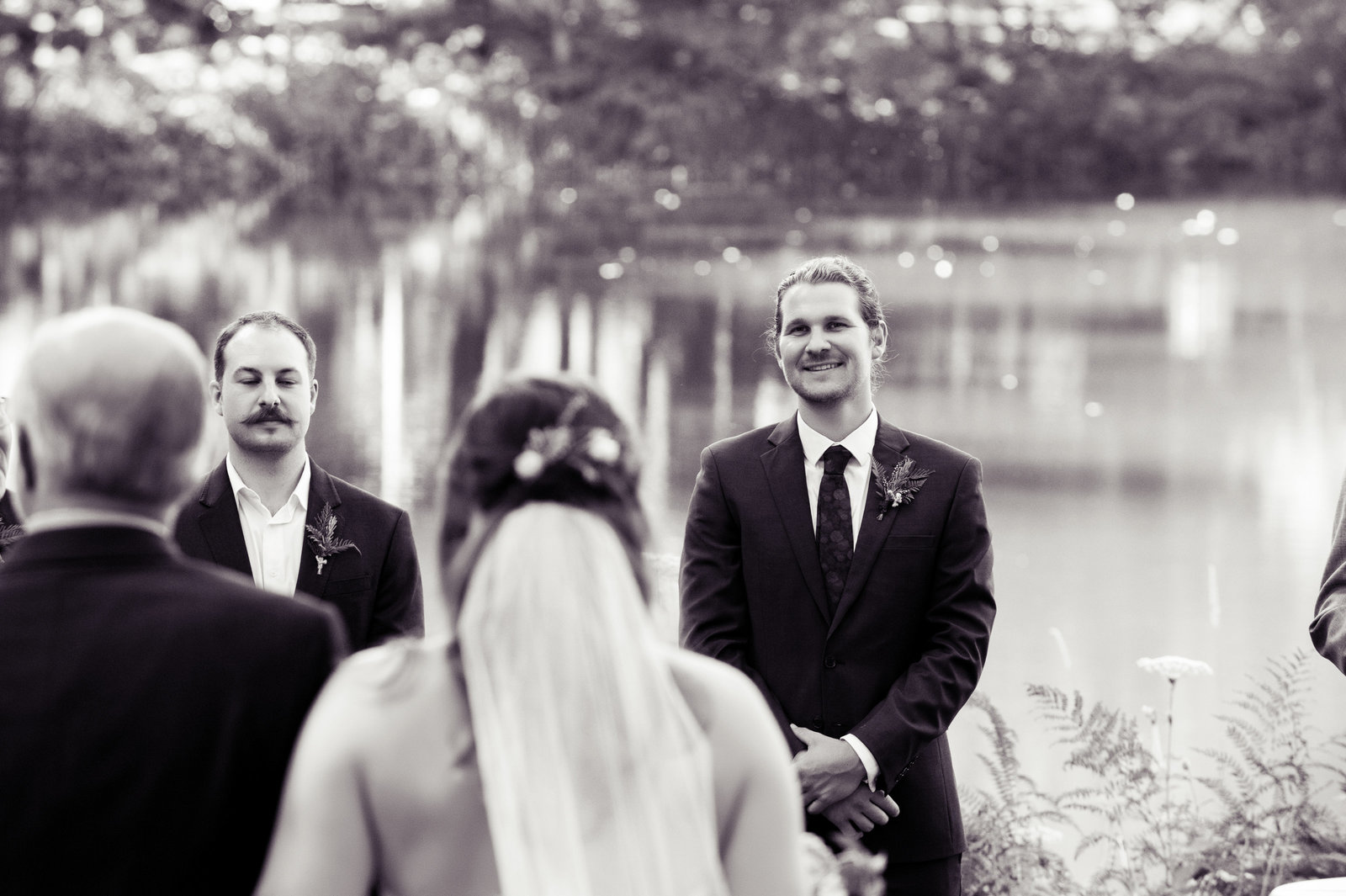 groom smiles at bride as she walks down the aisle with her father