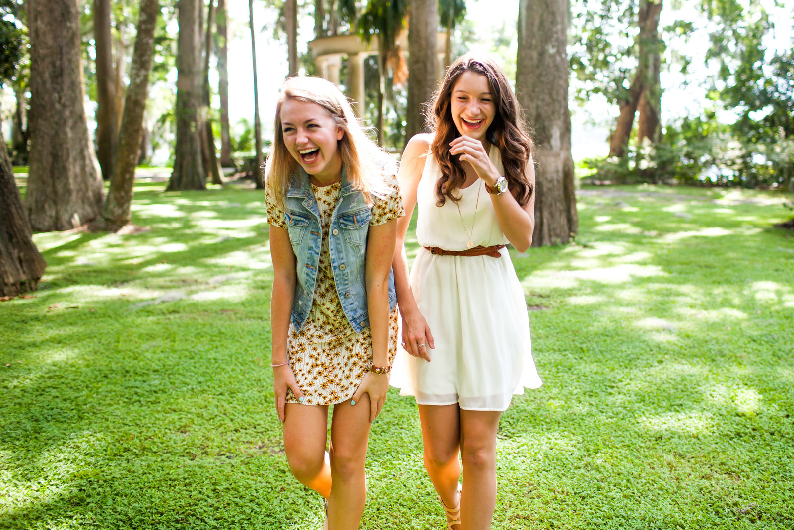 Best friends laughing in a green field in Winter Park Florida