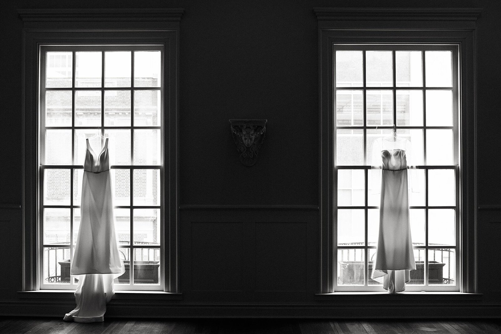 Two brides dresses in the windows of the Kansas City Club
