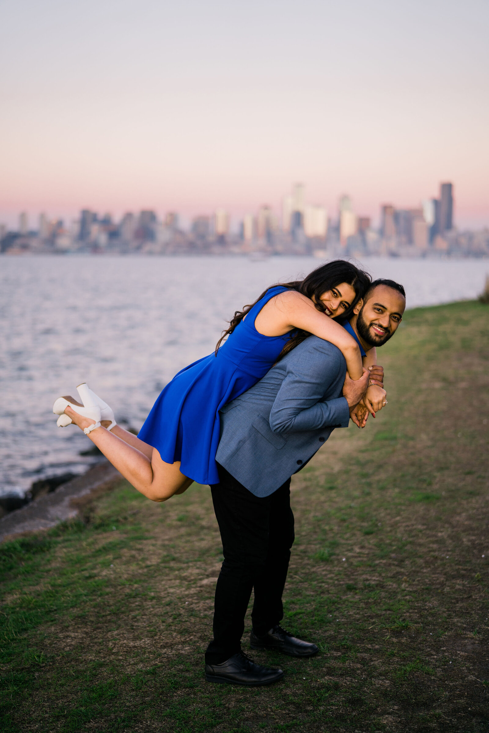 Bride hugs groom with Seattle skyline at dusk, near Luna Park in West Seattle and Alki Beach, the best spot for engagement photos in Seattle