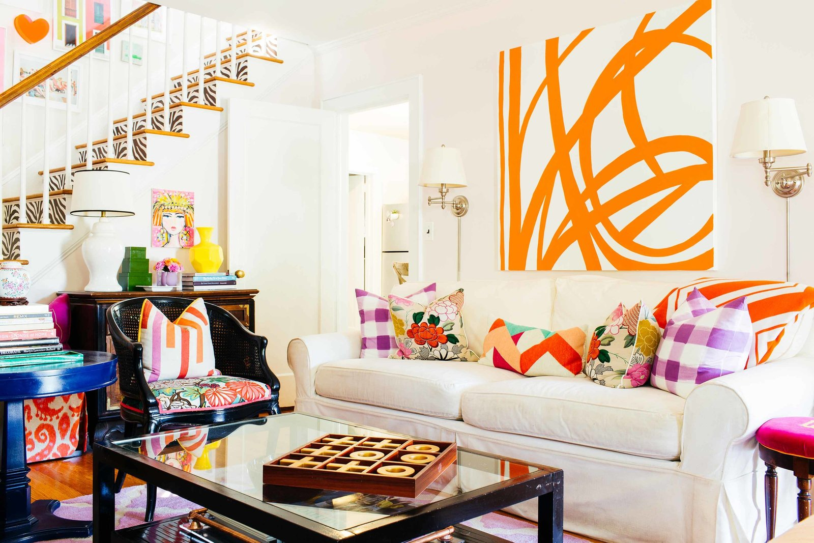 A living room with a large orange and white abstract painting.